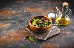 Fresh salad mix of baby spinach, arugula leaves and chard. In wooden bowl, healthy food stock image