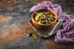 Fresh salad mix of baby spinach, arugula leaves and chard. In wooden bowl, healthy food royalty free stock images