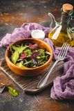 Fresh salad mix of baby spinach, arugula leaves and chard. In wooden bowl, healthy food stock photography
