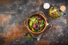 Fresh salad mix of baby spinach, arugula leaves and chard. In wooden bowl, healthy food, top view royalty free stock image