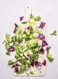 Fresh salad mix on a cutting board wooden rustic background top view Stock Photos