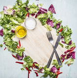 Fresh salad mix with salt and oil, knife and fork laid out around a cutting board  place for text,frame on wooden rustic backgroun Stock Photos