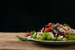 Fresh salad with mixed greens, radish, cucumber, tomato, onion, bell pepper. Basil, mint and other spices in bowl on wooden table  on black background with Stock Photos