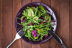 Fresh salad with mixed greens & x28;arugula, mesclun, mache& x29; on dark wooden background top view. Stock Photos
