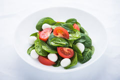 Fresh salad with mozzarella cheese, tomato and spinach on white paper background close up Royalty Free Stock Images