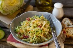 Fresh salad of napa cabbage with carrots, cucumber and salami. Fresh vegetable salad of napa cabbage with carrots, cucumber and salami royalty free stock images
