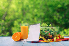 Fresh salad, orange juice, measuring tape with a empty notebook Royalty Free Stock Photography