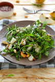 Fresh salad with pear, arugula and nuts Royalty Free Stock Image