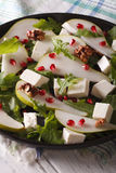 Fresh salad with pears, pomegranates, cheese and greens close up Stock Image