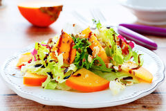Fresh salad with persimmons and nuts stock photos
