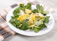 Fresh salad with pine nuts. Fresh lettuce on a plate, orange, feta cheese and pine nuts Royalty Free Stock Image