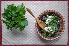 Fresh salad. With plums and cottage cheese and a spoon on white background royalty free stock photo