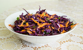 Fresh salad - red cabbage, carrots and parsley on a white plate and decorated cover - side view Stock Photography