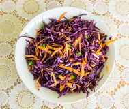 Fresh salad - red cabbage, carrots and parsley on a white plate and decorated cover - top view Royalty Free Stock Images