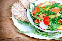Fresh salad and rice galettes (rice cakes). Fresh salad and rice cakes (rice galettes) - vegetarian food Royalty Free Stock Images