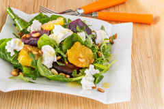 Fresh salad with roasted beetroot, cheese, orange and pine nuts. Fresh salad with roasted beetroot, white cheese, orange and pine nuts with orange fork and knife Royalty Free Stock Photography