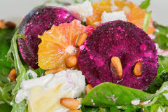 Fresh salad with roasted beetroot, goat cheese, orangeand pine n. Salad with roasted beetroot, goat cheese, orangeand pine nuts, close-up Royalty Free Stock Images