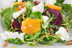 Fresh salad with roasted beetroot, white cheese, orange, nuts. Fresh salad with roasted beetroot, white cheese, orange, and pine nuts, close-up Stock Images