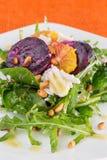 Fresh salad with roasted beetroot, white cheese, o. Range and pine nuts, close-up, on orange background Stock Photo