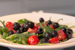 Fresh salad with ruccola, tomatoes and black olives on a deep pl Stock Images