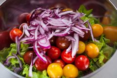 Fresh salad with rucola, tomatoes cherry, feta cheese and red onion in a bowl. top view stock image