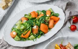 Fresh salad with salmon fish, cucumbers, feta cheese, carrots, lettuce, spinach and sauce on plate over light wooden background.