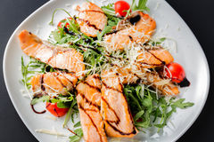 Fresh salad of salmon pieces, cherry tomatoes, lettuce, cheese and sauce on a white plate close up Stock Photo