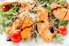 Fresh salad of salmon pieces, cherry tomatoes, lettuce, cheese and sauce on a white plate close up Stock Images