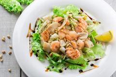 Fresh salad with shrimp, salmon, squid, avocado and nuts on whit Stock Photos