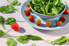 Fresh salad with spinach and strawberries on wooden light pink table Stock Image