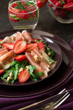 Fresh salad with strawberry, arugula and prosciutto. On purple plate. Low key Royalty Free Stock Photos