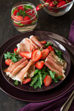 Fresh salad with strawberry, arugula and prosciutto. On purple plate. Low key Royalty Free Stock Photography