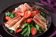 Fresh salad with strawberry, arugula and prosciutto. On purple plate. Low key Stock Photos