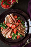 Fresh salad with strawberry, arugula and prosciutto. On purple plate. Low key Royalty Free Stock Image