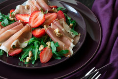 Fresh salad with strawberry, arugula and prosciutto. On purple plate. Low key Royalty Free Stock Photo