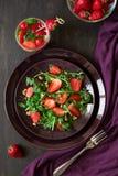 Fresh salad with strawberry, arugula and walnuts. On purple plate. Low key Stock Photos