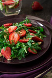 Fresh salad with strawberry, arugula and walnuts. On purple plate. Low key Royalty Free Stock Photos