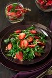 Fresh salad with strawberry, arugula and walnuts. On purple plate. Low key Stock Photo