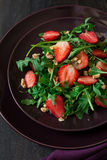Fresh salad with strawberry, arugula and walnuts. On purple plate. Low key Royalty Free Stock Image