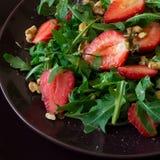 Fresh salad with strawberry, arugula and walnuts. On purple plate. Low key Stock Image