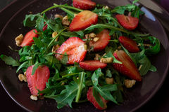 Fresh salad with strawberry, arugula and walnuts. On purple plate. Low key Stock Images