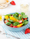 Fresh salad with strawberry, orange and spinach in a bowl on wooden background Stock Images