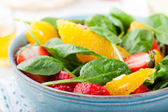 Fresh salad with strawberry, orange and spinach in a bowl on wooden background Royalty Free Stock Photos