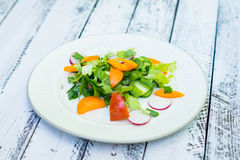 Fresh salad with summer vegetables on the wooden table Royalty Free Stock Images