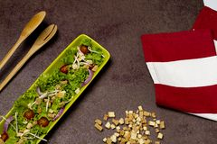 Fresh salad of tomato lettuce and onion with red striped cloth, bread laces and wooden spoon stock photo