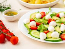 Fresh salad with tomatoes cucumbers arugula mozzarella and avocado. Oil with spices rosemary thyme, side view. Fresh salad with tomatoes cucumbers arugula royalty free stock photos