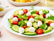 Fresh salad with tomatoes cucumbers arugula mozzarella and avocado. Oil with spices rosemary thyme, side view close up.  stock photo
