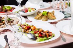 Fresh salad with tomatoes and meat. Delicious prepared and decorated food on table in restaurant. royalty free stock image