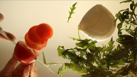 Fresh salad of tomatoes, mozzarella and arugula. hands closeup stock video
