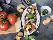 Fresh salad of tomatoes and mozzarella. Recipe with olive oil with red onion, olives and basil Stock Photography